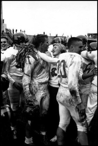 USA. Seattle, Washington. 1955. The head cheerleader and the football captain embrace after a game. Their team had just won a game for the first time in three years., by Burt Glinn