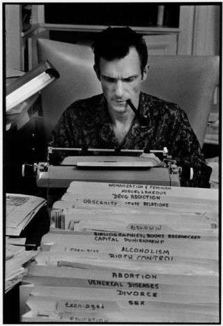 USA. Chicago, IL. 1966. Hugh Hefner, Playboy founder, typing at his desk in his mansion., by Burt Glinn