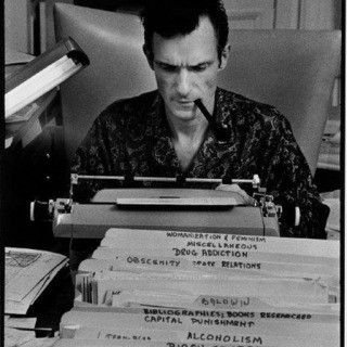 Burt Glinn, USA. Chicago, IL. 1966. Hugh Hefner, Playboy founder, typing at his desk in his mansion.