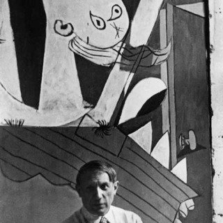 "David Seymour, Spanish painter Pablo Picasso in front of his painting ""Guernica"", at its unveiling at the Spanish Pavilion of the International World Fair held six weeks after the aerial bombing of the Basque village of Guernica."