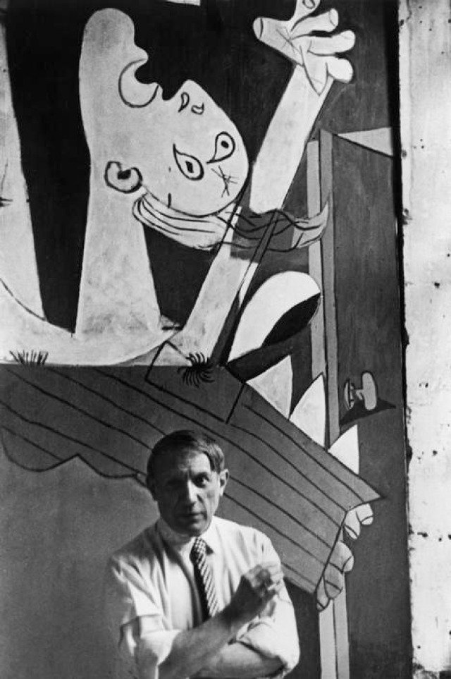 David Seymour, Spanish painter Pablo Picasso in front of his painting &quot;Guernica&quot;, at its unveiling at the Spanish Pavilion of the International World Fair held six weeks after the aerial bombing of the Basque village of Guernica.