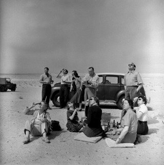 Total Eclipse of the Sun. Kuwaiti Oil Company personel and their families bring a picnic lunch to the desert to watch the eclipse. 1952., by George Rodger